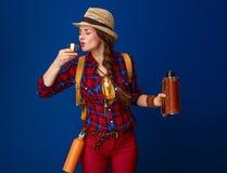 喝从热水瓶的旅游妇女热的饮料 免版税库存图片