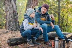 喝从热水瓶的父亲和儿子热的茶 免版税图库摄影