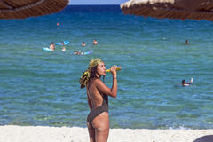 喝从玻璃瓶的女孩在海滩 库存图片