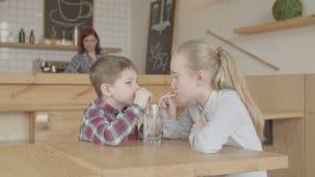 喝从玻璃的孩子通过在咖啡馆的秸杆 股票录像