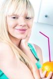 喝从秸杆的华美的女孩一个桔子 免版税库存照片