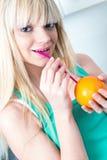 喝从秸杆的女孩一个桔子 库存照片