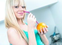 喝从秸杆的迷人的女孩一个桔子 免版税库存照片