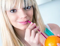 喝从秸杆的逗人喜爱的女孩一个桔子 库存图片