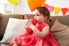 喝从sippy杯子的女婴在生日 库存图片
