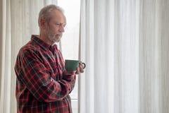喝他的咖啡和看在外面的体贴的成熟人 免版税库存照片