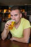 喝低度黄啤酒的人在客栈 库存图片