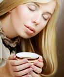 喝俏丽的妇女的咖啡 库存照片