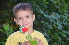喝健康鸡尾酒果汁圆滑的人的逗人喜爱的男孩在夏天 享受有机饮料的愉快的孩子 免版税图库摄影