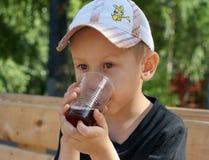 喝冷的饮料的小男孩 库存照片