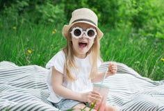 喝可口草莓圆滑的人用牛奶和冰淇淋的女孩 免版税库存图片