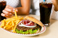 喝吃汉堡包碳酸钠二名妇女 免版税库存照片