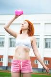 喝和倾吐水的美丽的运动的红发女孩在体育以后 免版税库存图片