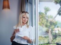 喝和凝视在视窗外面的女商人 库存图片