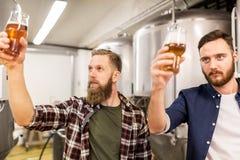 喝和测试工艺啤酒的人在啤酒厂 免版税库存图片