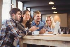 喝咖啡和指向在膝上型计算机屏幕上的微笑的朋友 库存照片
