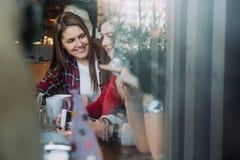 喝咖啡和聊天在咖啡馆的两名美丽的妇女 免版税库存照片