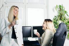 喝咖啡和谈论的女性同事 库存照片