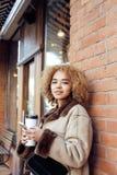 喝咖啡外面在咖啡馆,现代女商人生活方式概念的年轻俏丽的非裔美国人的妇女 库存照片