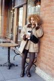 喝咖啡外面在咖啡馆,现代女商人生活方式概念的年轻俏丽的非裔美国人的妇女 图库摄影