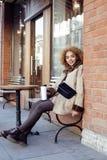 喝咖啡外面在咖啡馆,现代女商人生活方式概念的年轻俏丽的非裔美国人的妇女 免版税图库摄影