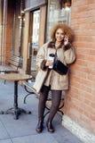 喝咖啡外面在咖啡馆,现代女商人生活方式概念的年轻俏丽的非裔美国人的妇女 免版税库存照片