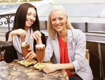 喝咖啡开会的微笑的妇女 免版税图库摄影