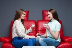 喝咖啡的两个笑的女朋友 库存图片