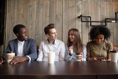 喝咖啡的微笑的多种族朋友获得乐趣在咖啡馆 库存照片