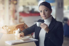 喝咖啡的微笑的妇女 库存照片
