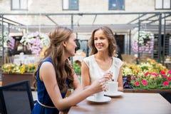 喝咖啡的微笑的少妇在街道咖啡馆 免版税库存图片