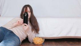 喝啤酒和吃芯片的年轻美丽的妇女放置在地板在长沙发附近 在瓶读标签 股票视频
