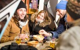 喝啤酒和吃芯片的愉快的朋友在滑雪胜地瑞士山中的牧人小屋 库存图片