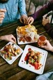 喝啤酒和吃食物特写镜头的人 免版税库存照片