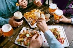 喝啤酒和吃食物特写镜头的人 库存照片