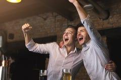 喝啤酒和呼喊在酒吧的成功的商人 图库摄影