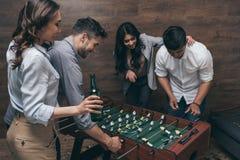 喝啤酒和演奏foosball的年轻朋友户内 免版税库存照片