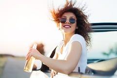 喝啤酒和看日落的少妇 她在一辆嬉戏汽车坐 免版税图库摄影