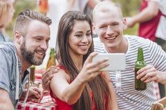 喝啤酒和采取selfie的愉快的朋友在格栅党期间 库存照片