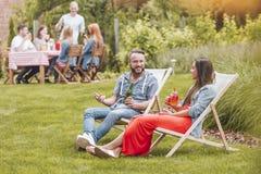喝啤酒和鸡尾酒的微笑的朋友,当放松在sunbeds在庭院里时 免版税库存照片