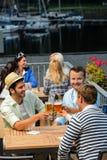 喝啤酒的三个人在大阳台酒吧 库存照片