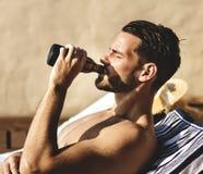 喝啤酒的人由水池 免版税库存图片