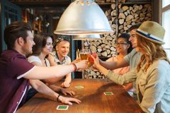 喝啤酒的愉快的朋友在酒吧或客栈 免版税图库摄影