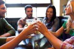 喝啤酒的愉快的朋友在酒吧或客栈 免版税库存图片