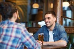喝啤酒的愉快的男性朋友在酒吧或客栈 免版税图库摄影