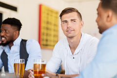 喝啤酒的愉快的男性朋友在酒吧或客栈 免版税库存照片