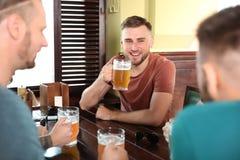 喝啤酒的朋友在桌上 免版税库存照片