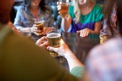 喝啤酒的朋友在酒吧或客栈 免版税库存照片