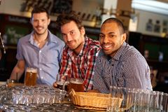 喝啤酒的年轻人在酒吧柜台 免版税库存图片