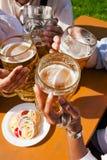 喝四个朋友组的啤酒 免版税库存图片